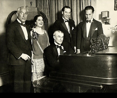 Birthday party honoring Maurice Ravel in New York City, March 8, 1928. From left - Oskar Fried; Éva Gauthier; Ravel at piano; Manoah Leide-Tedesco; and George Gershwin