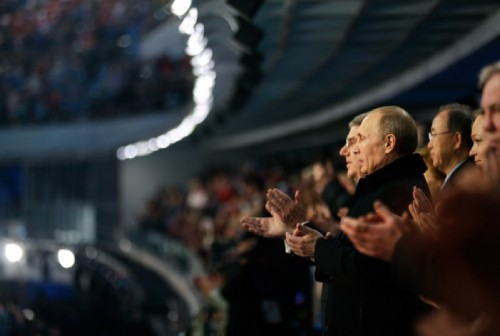 Russian President Vladimir Putin and International Olympic Committee President Thomas Bach applaud after singing the Russian national anthem on February 7, 2014.