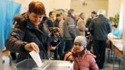 A woman casts her vote while holding her dog at a polling station on March 16, 2014 in Simferopol