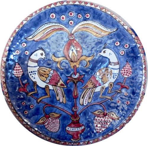 A series of handmade ceramic plates with ancient Russian themes the tree of life, a peacock or a firebird and, of course, a fire-mane horse