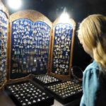 A girl looking at the stand with folk jewelry of Russian craftsmen