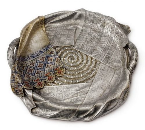 Sazikov jewelry company. Large silver tray trompe l'oeil in the form of a basket of spirally twisted rope, covered with an embroidered towel. The patterns and the inscription on the towel are made using champlevé enamel technique. Diameter 51 cm.Moscow, 1877