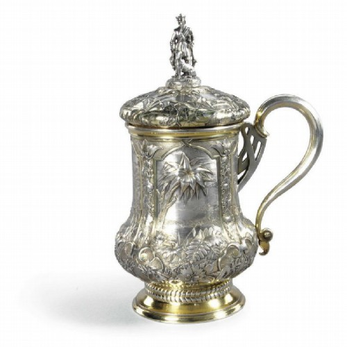 Silver mug with lid, gilded, patterned with lush vegetation and landscape. The lid is crowned with a molded tip in the shape of a hunter with a dog. Pavel Ovchinnikov, Moscow, 1866