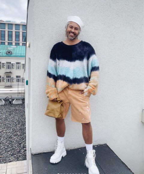 Stylish Alexander Rogov in white boots and a striped sweater